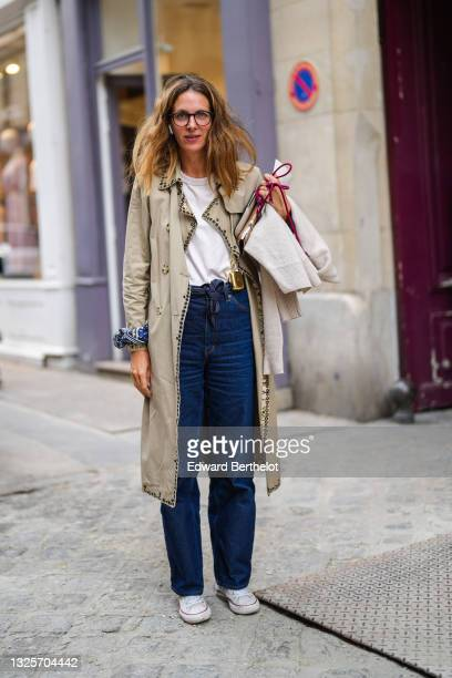 Guest wears glasses, a white t-shirt, a navy blue scarf as a belt, blue denim jeans mom pants, a long beige nailed / studded trench coat, a blue and...