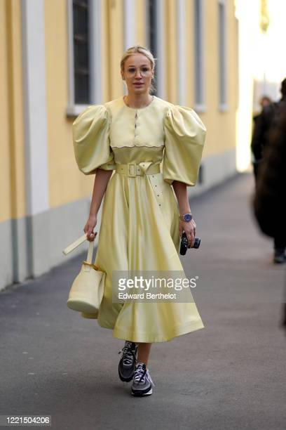 Guest wears glasses, a yellow lustrous silky dress with puff sleeves, a belt, sneakers, outside Tod's, during Milan Fashion Week Fall/Winter...
