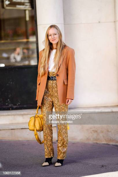 A guest wears glasses an orange blazer jacket a white tshirt a belt snake print pants a yellow bag outside Chloe during Paris Fashion Week Womenswear...