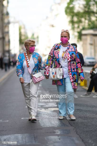 Guest wears glasses, silver necklaces, a white shirt, a blue with pink / orange / beige and green flower print patter bomber coat, a white watch,...