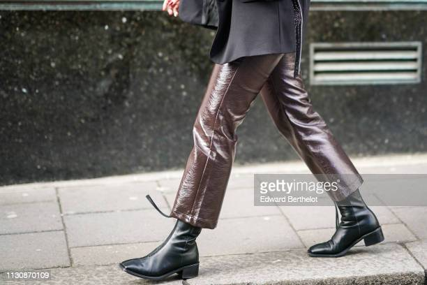 A guest wears glossy brown pants black boots during London Fashion Week February 2019 on February 19 2019 in London England