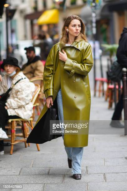 Guest wears gold and diamond earrings with pendants, a white t-shirt, blue faded denim flared jeans pants, a green / khaki shiny leather long jacket...