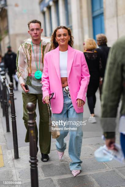 Guest wears gold earrings, a white halter crop-top / t-shirt, white sunglasses, a long oversized fuchsia / pink blazer jacket, silver rings, blue...