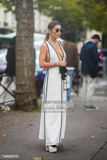 Guest wears gold earrings from Chanel, sunglasses, a white V-neck long flowing dress with black stripes tank-top dress, a gold Love bracelet from...
