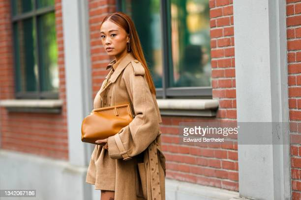 Guest wears gold large pendant earrings from Fendi, a gold large chain FF necklace from Fendi, a brown with black stripes and FF monogram embroidered...