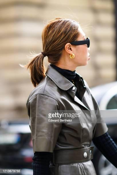 Guest wears golden earrings, a turtleneck top, a khaki leather dress, outside Altuzarra, during Paris Fashion Week - Womenswear Fall/Winter...