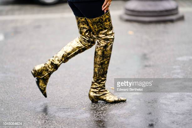 A guest wears golden shiny boots outside Chanel during Paris Fashion Week Womenswear Spring/Summer 2019 on October 2 2018 in Paris France