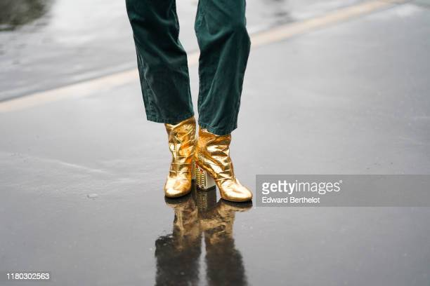Guest wears golden shiny boots, outside Chanel, during Paris Fashion Week - Womenswear Spring Summer 2020, on October 01, 2019 in Paris, France.