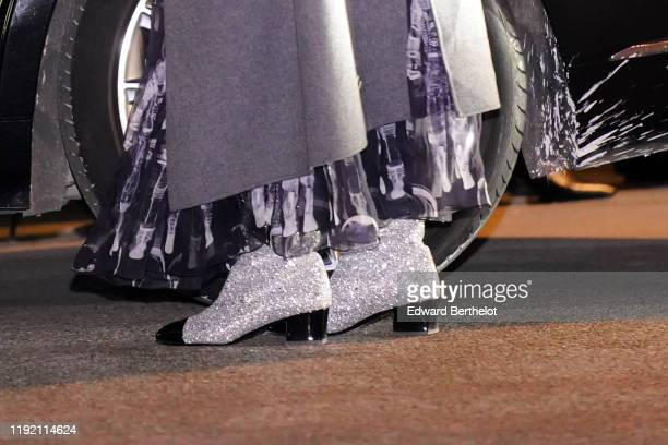 Guest wears gray glitter shiny boots, after the Chanel Metiers D'Art 2019-2020 at the Grand Palais, on December 04, 2019 in Paris, France.
