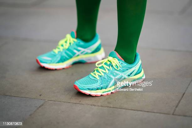A guest wears green and neon yellow sneakers shoes during London Fashion Week February 2019 on February 19 2019 in London England