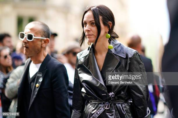 A guest wears green earrings and a black pvc trench coat outside Dior during Paris Fashion Week Menswear SpringSummer 2019 on June 23 2018 in Paris...
