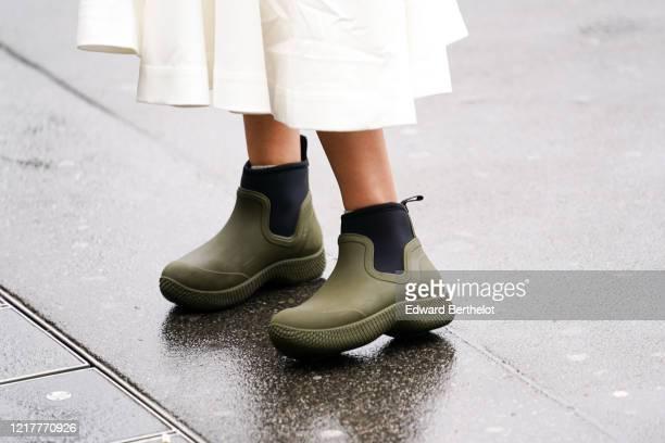 Guest wears green khaki rain rubber boots, outside Ann Demeulemeester, during Paris Fashion Week - Womenswear Fall/Winter 2020/2021, on February 27,...