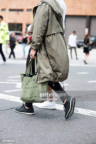 Guest wears green military overoat green canvas Marc Jacobs tote and black nike sneakers after Rebecca Minkoff SS16 at Skylight Clarkson sq during...
