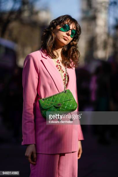 A guest wears green sunglasses a pink blazer jacket a green Chanel bag during London Fashion Week February 2018 on February 16 2018 in London England