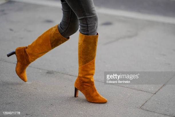 A guest wears grey skinny ripped jeans tancolor suede heeled knee high boots outside Chanel during Paris Fashion Week Haute Couture Spring/Summer...
