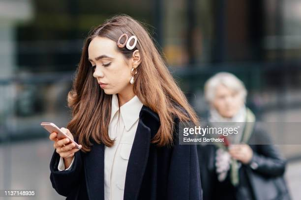 A guest wears hair clips earrings a white jacket a black coat during London Fashion Week February 2019 on February 16 2019 in London England