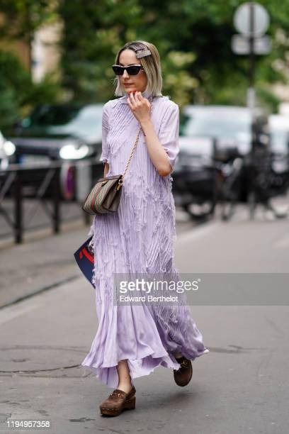 A guest wears hair clips sunglasses a Gucci crossbody bag a long pleated ripped hem flowing mauve dress brown slingback clogs outside OffWhite during...