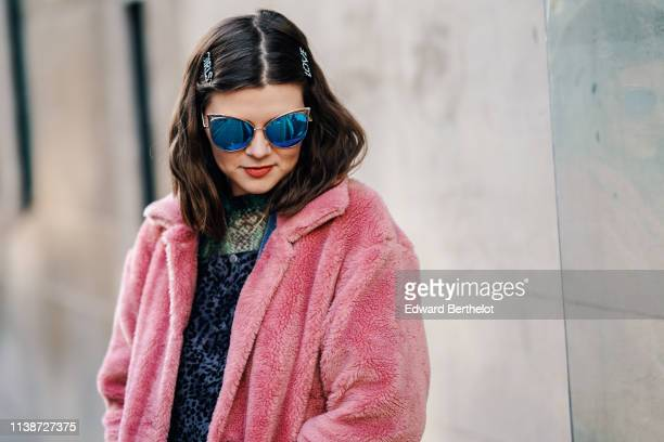 A guest wears hair clips sunglasses a pink fluffy coat during London Fashion Week February 2019 on February 15 2019 in London England