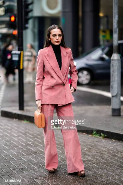 A guest wears hair pins a black turtleneck a pink doublebreasted pantsuit with flare pants a gold leather handbag brown python pattern platform boots...