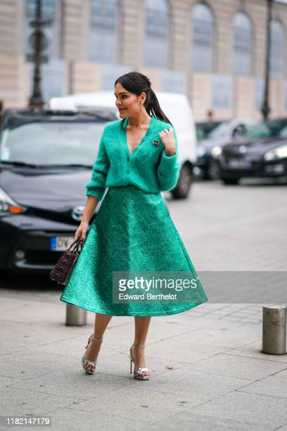 Guest wears hair pins, a green fluffy V-neck top, a lustrous green lamed skirt, a brooch, a burgundy Dior Lady Dior bag, shiny metallic tone strappy...