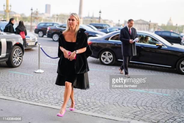 A guest wears hair pins earrings a black velvet offtheshoulder dress a black fluffy coat a pink clutch pink bejewelled heeled pumps on April 12 2019...