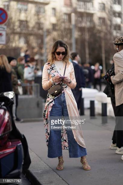 Guest wears hairpins, sunglasses, pearl earrings, a white top, a flowing beige coat with a colorful floral print side, a brown alligator pattern...
