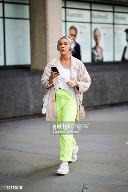 A guest wears headphones from Bose a piercing on the lip a white top neon green sport pants a beige trench coat beige and white sneakers during...