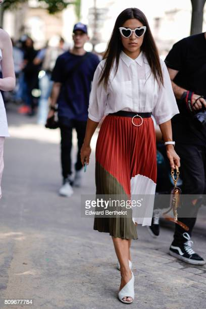 A guest wears heart shaped sunglasses a white shirt a red white and green ruffled skirt white shoes outside the Jean Paul Gaultier show during Paris...