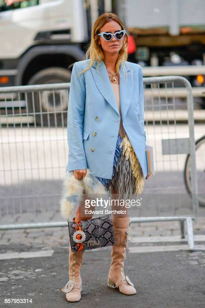 A guest wears heart sunglasses a blue blazer jacket a bag boots fur outside Miu Miu during Paris Fashion Week Womenswear Spring/Summer 2018 on...