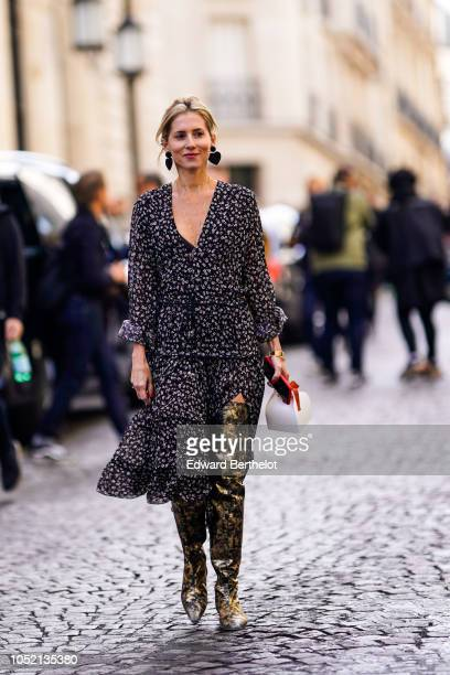 Guest wears heart-shaped earrings, a ruffled pleated black and white dress, golden thigh high boots, outside Altuzarra, during Paris Fashion Week...