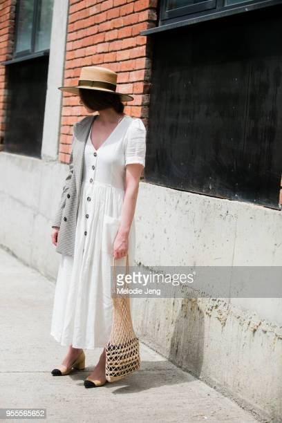 A guest wears her blazer off one shoulder a white summer dress net bag with another bag inside and summer straw hat at MercedesBenz Fashion Week...