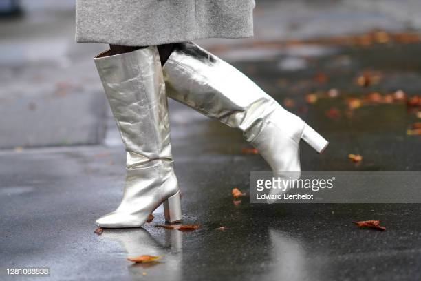 Guest wears high heels pointy silver shiny boots, outside Chanel, during Paris Fashion Week - Womenswear Spring Summer 2021, on October 06, 2020 in...