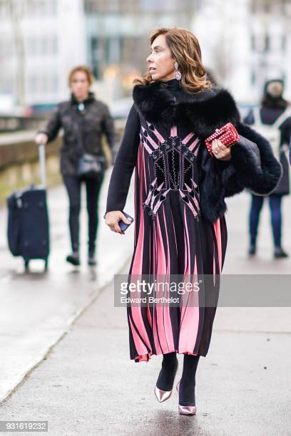 A guest wears huge earrings a black fur collar a pink and black long pleated embroidered dress a red studded clutch black tights shiny pink pumps...