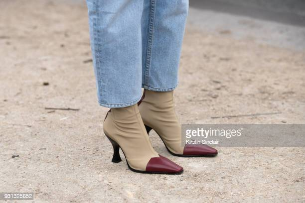 A guest wears jeans and Celine boots day 2 of Paris Womens Fashion Week Spring/Summer 2018 on February 27 2018 in London England