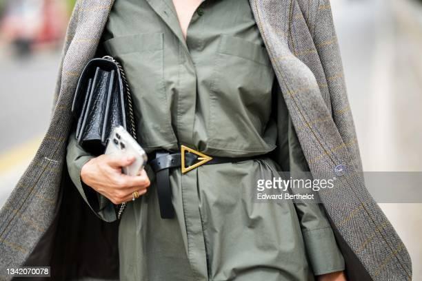 Guest wears khaki oversized long shirt dress, a gray and white print pattern oversized blazer jacket, a black shiny leather belt from Bottega Veneta,...