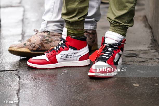 A guest wears khaki sport pants with elasticated hem red and white OffWhite for Nike Air Jordan 1 sneakers outside Giambattista Valli during Paris...