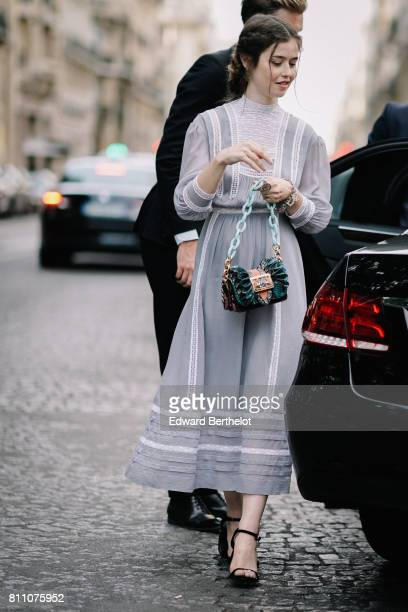 A guest wears lace ruffle dress a bag with a green chain sandals heels shoes outside the Vogue foundation dinner during Paris Fashion Week Haute...