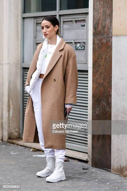 A guest wears large creole earrings a white puffy jacket a camel coat white pants with drawstring offwhite booties during Paris Fashion Week...