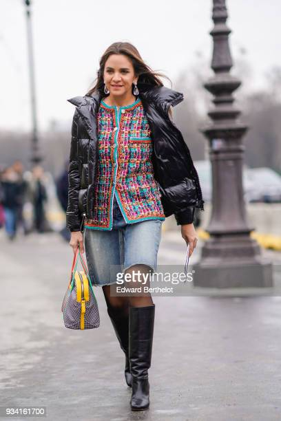 A guest wears large crystal earrings a glossy black puffy jacket a multicolor tweed jacket a ripped denim skirt a yellow lined studded handbag black...
