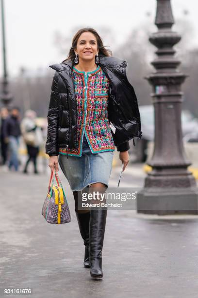 A guest wears large crystal earrings a glossy black puffy jacket a muticolor tweed jacket blue ripped denim skirt a yellow lined studded handbag...