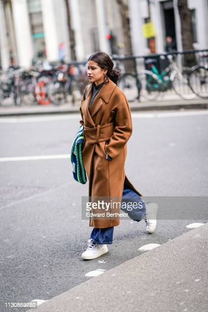 A guest wears large earrings a grey turtleneck a camel coat with a large belt a green and navy blue scarf denim flare pants white and beige Nike...