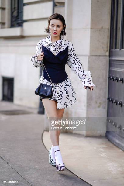 A guest wears large earrings a white and black pattern asymmetric mini dressshirt a black corset a black purse white socks black and white striped...