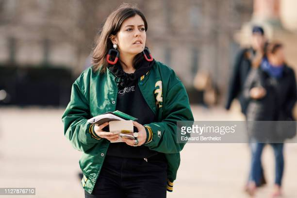 A guest wears large red black and white earrings a black sweatshirt a shiny green bomber jacket outside OffWhite during Paris Fashion Week Menswear...