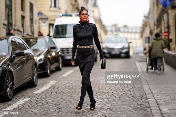 A guest wears large red earrings a large necklace a black highneck and long sleeves column dress black suede peep toe highheeled boots during Paris...