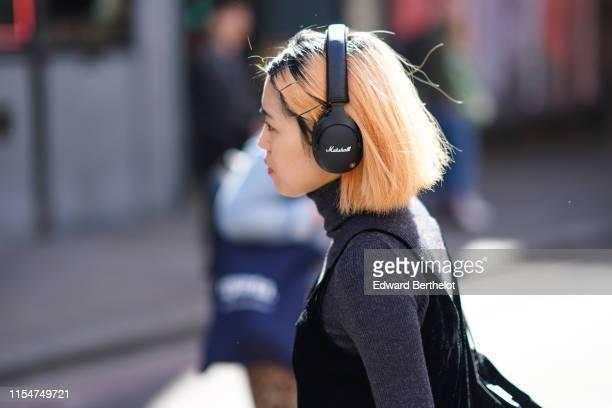 Guest wears Marshall headphones, a gray wool top turtleneck, during London Fashion Week Men's June 2019 on June 08, 2019 in London, England.