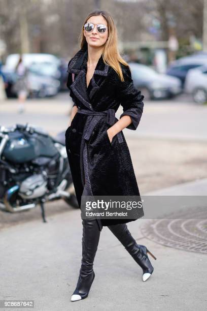 A guest wears mirror sunglasses a black coat a Chanel silver bag black leather thigh high boots outside Chanel during Paris Fashion Week Womenswear...