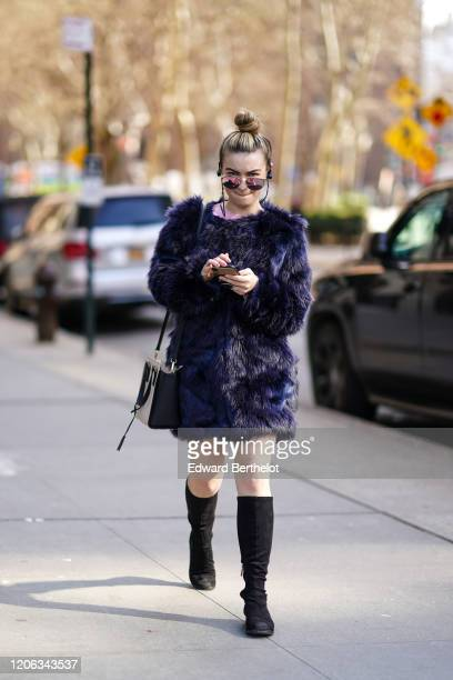 A guest wears mirror sunglasses a dark blue fluffy faux fur coat a bag black boots during New York Fashion Week Fall Winter 2020 on February 12 2020...