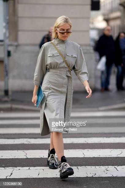 Guest wears mirror sunglasses, a gray dress, black shoes with white shoelace, a crossbody bag with a golden chain, outside Sportmax, during Milan...