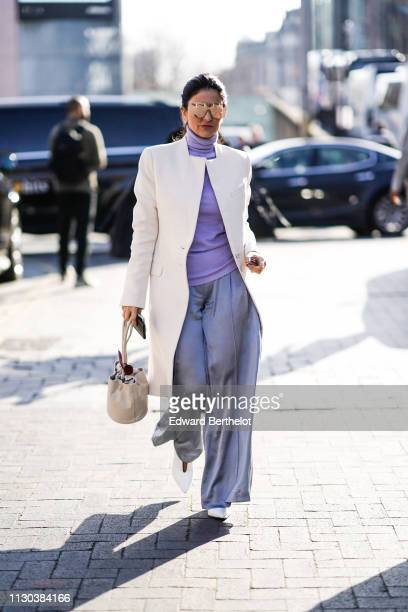 A guest wears mirror sunglasses a purple turtleneck a white coat gray flare pants a bag during London Fashion Week February 2019 on February 17 2019...