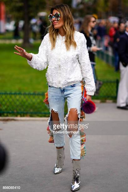 A guest wears mirror sunglasses a white pull over ripped jeans silver shoes outside Elie Saab during Paris Fashion Week Womenswear Spring/Summer 2018...